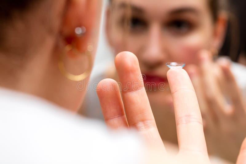 Plan rapproché, jeune femme avec un verre de contact regardant dans le miroir images stock