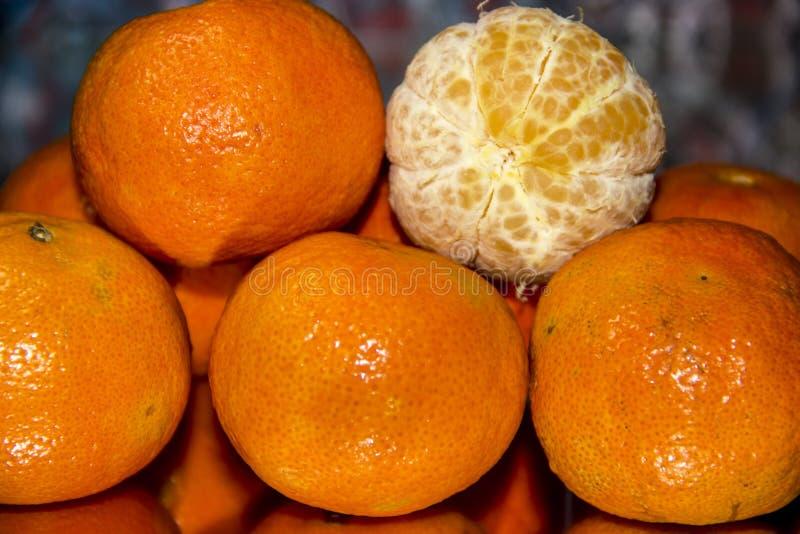 Plan rapproché non épluché de mandarines Avec une mandarine épluchée photographie stock libre de droits