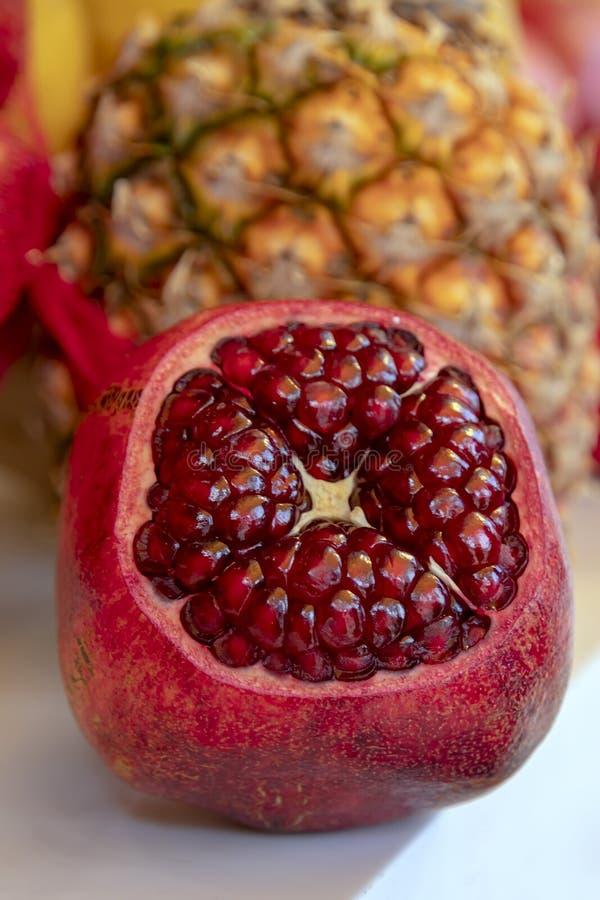 Plan rapproché ouvert de fruit de grenade sur un fond brouillé d'ananas photo stock