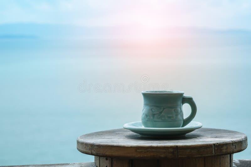 Plan rapproché par tasse de café sur la table sur le fond de vue de mer pendant le matin photographie stock libre de droits