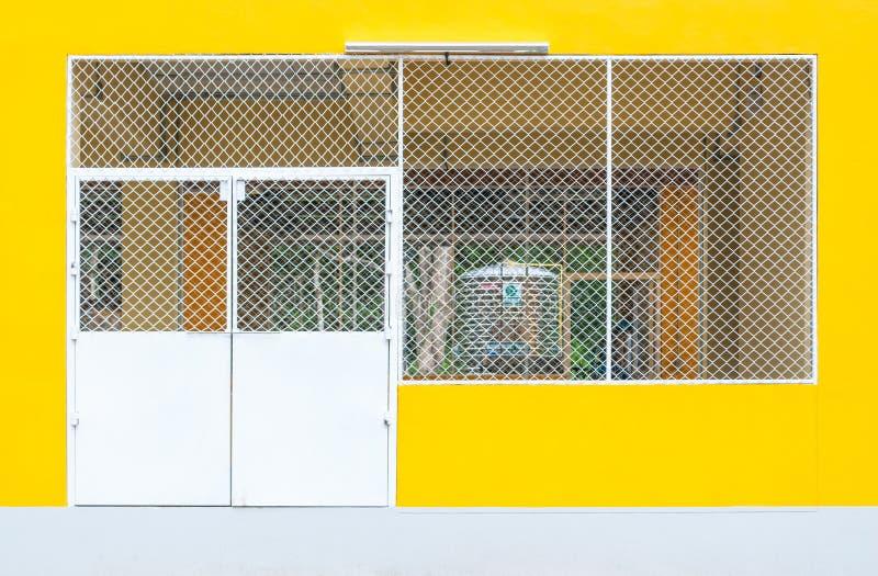 Plan rapproché pour metal la porte d'entrée de l'entrepôt jaune concret d'usine photographie stock libre de droits