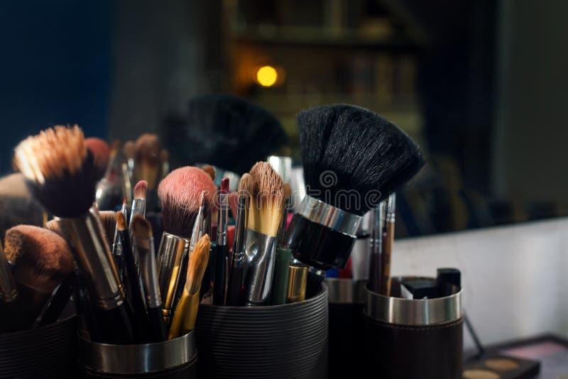 Plan rapproché professionnel de brosse de lecture de maquillage près de miroir de salon images stock