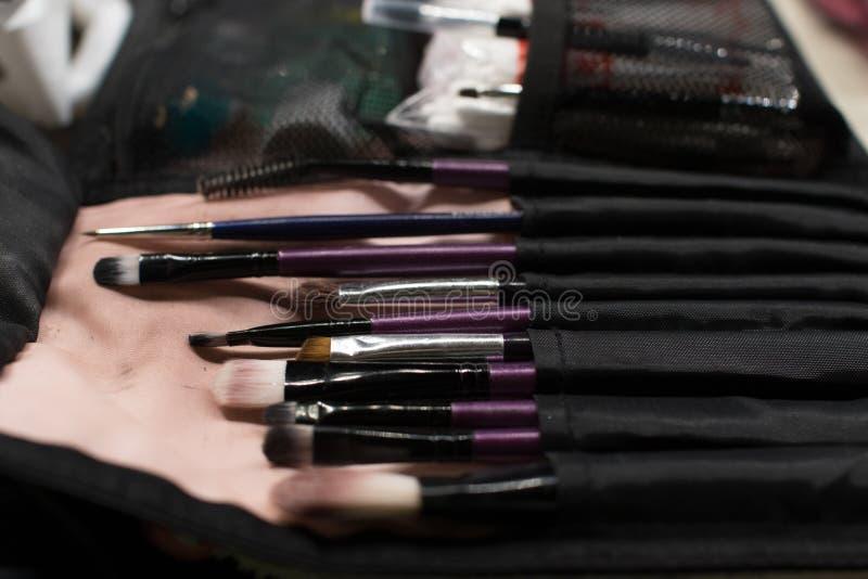 Plan rapproché professionnel de brosse de lecture de maquillage près de miroir de salon photos libres de droits