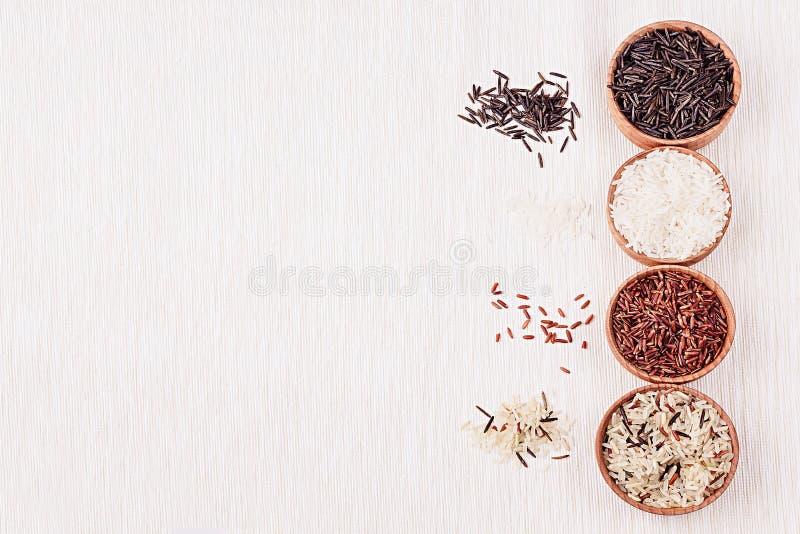 Plan rapproché rouge et noir et blanc de riz dans des cuvettes en bois sur le tissu beige images libres de droits