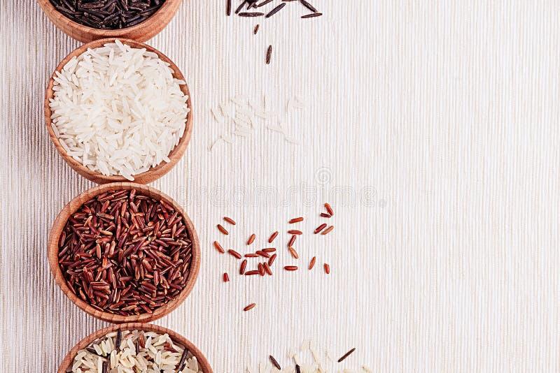 Plan rapproché rouge et noir et blanc de riz dans des cuvettes en bois sur le tissu beige photo stock