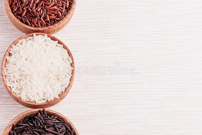 Plan rapproché rouge et noir et blanc de riz dans des cuvettes en bois sur le tissu beige image libre de droits