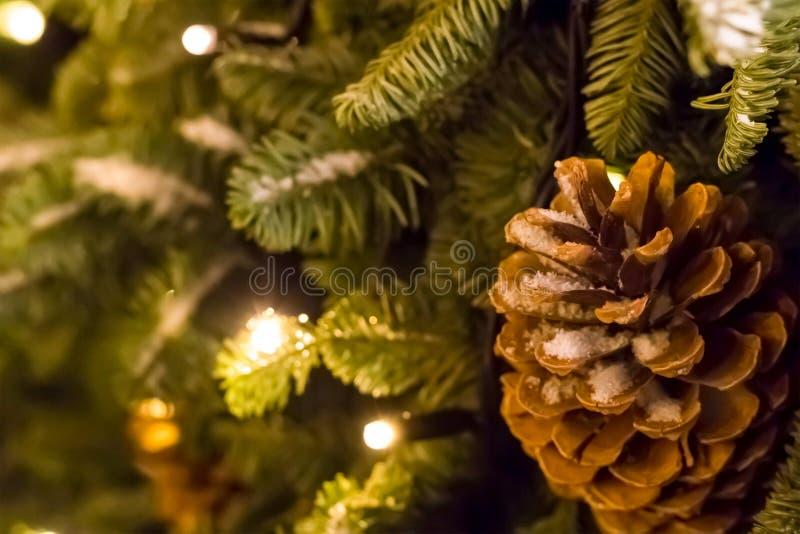 Plan rapproché rougeoyant de guirlande de Noël de fête de décoration de neige de cône de pin, Noël bas de carte de voeux Joyeux photos libres de droits
