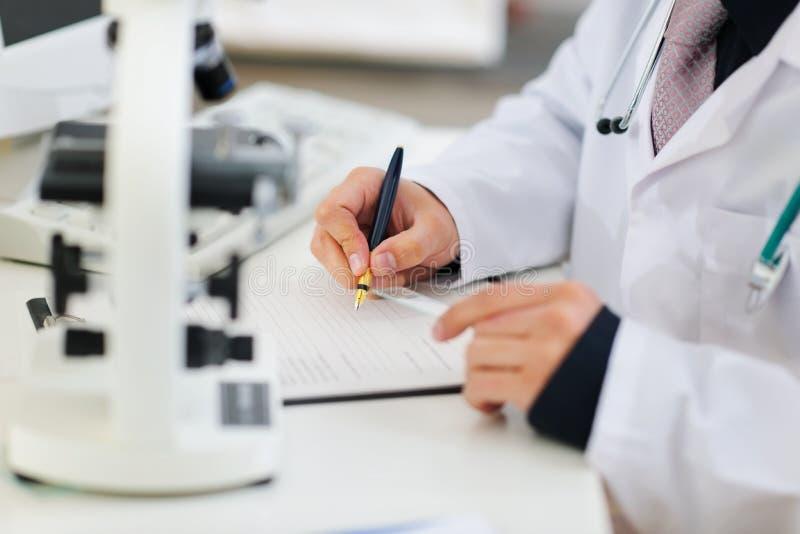 Plan rapproché sur des mains de docteur fonctionnant avec des documents image stock