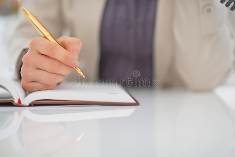 Plan rapproché sur l'écriture de femme d'affaires en journal intime image libre de droits