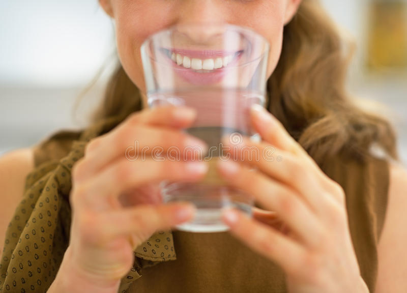Plan rapproché sur l'eau potable de jeune femme au foyer photo stock