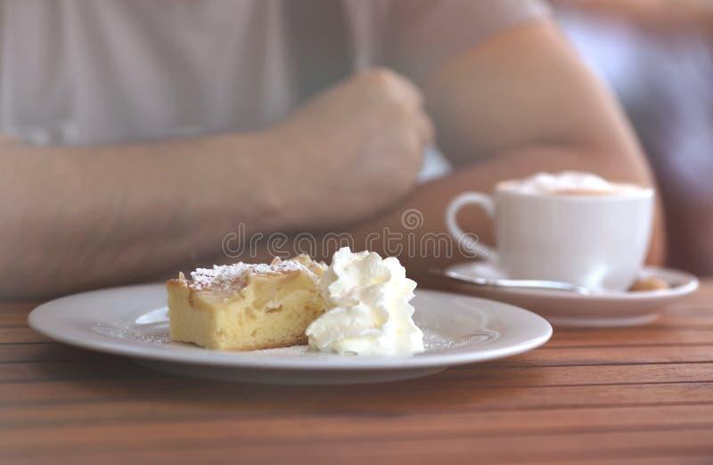 Plan rapproché sur l'homme s'asseyant en café ayant le morceau de gâteau doux crémeux photographie stock