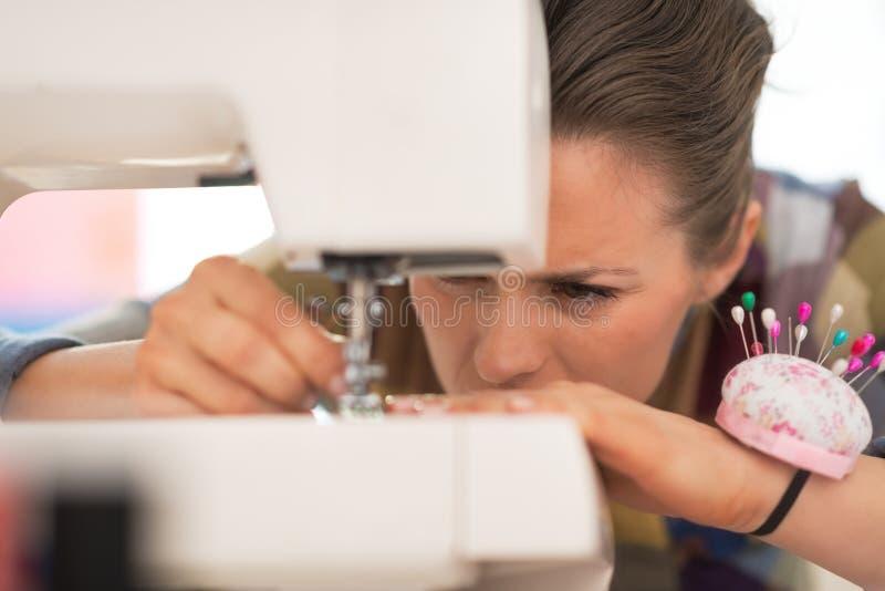 Plan rapproché sur l'ouvrière couturière travaillant avec la machine à coudre photo libre de droits