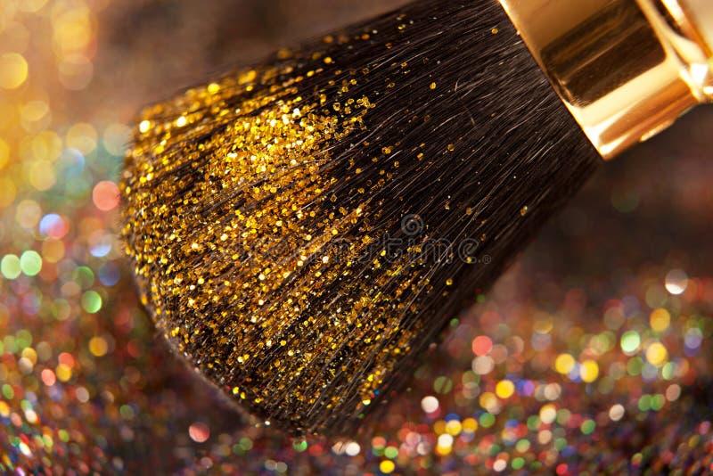 Plan rapproché sur la brosse d'or et la poudre brillante image libre de droits