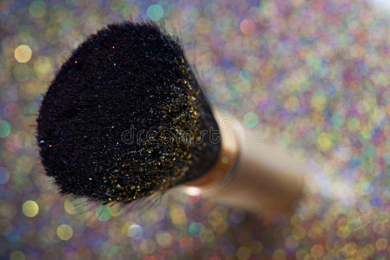 Plan rapproché sur la brosse d'or et la poudre brillante photo stock