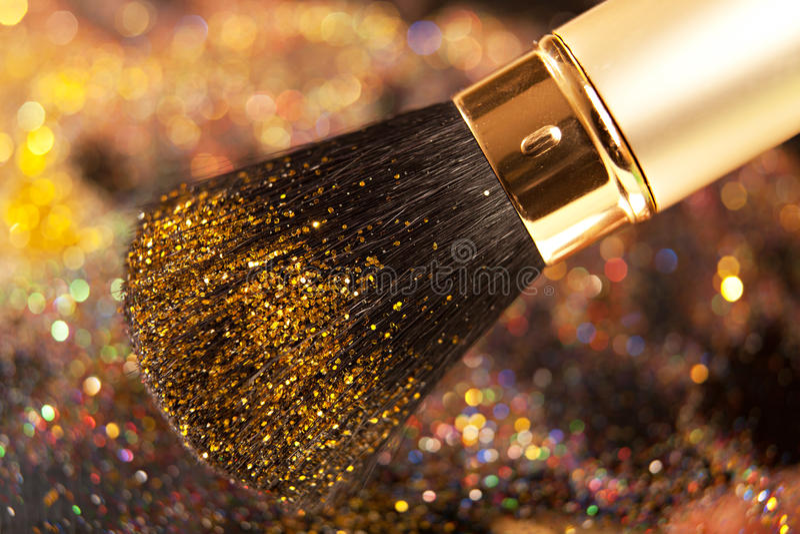 Plan rapproché sur la brosse d'or et la poudre brillante image stock