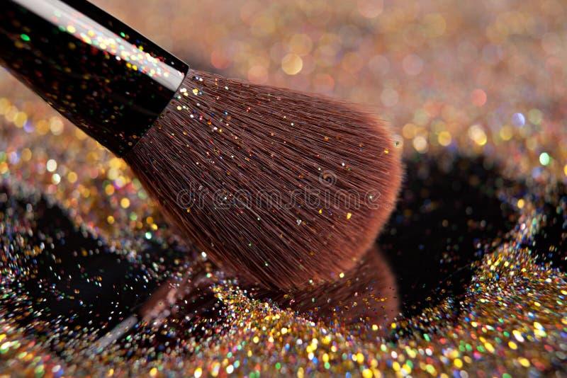 Plan rapproché sur la brosse d'or et la poudre brillante photos stock