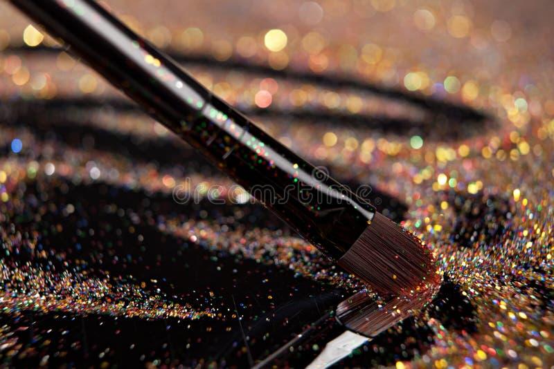 Plan rapproché sur la brosse d'or et la poudre brillante images libres de droits