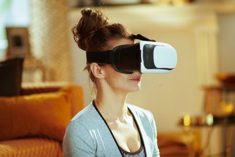 Plan rapproché sur la femme décontractée à la maison moderne méditant dans la vitesse de VR images libres de droits