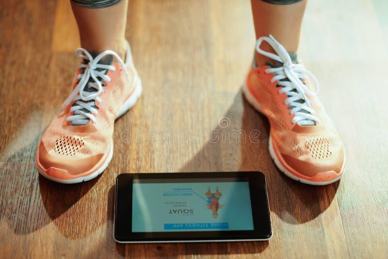 Plan rapproché sur la femme employant l'appli d'entraîneur de forme physique dans la tablette photo stock