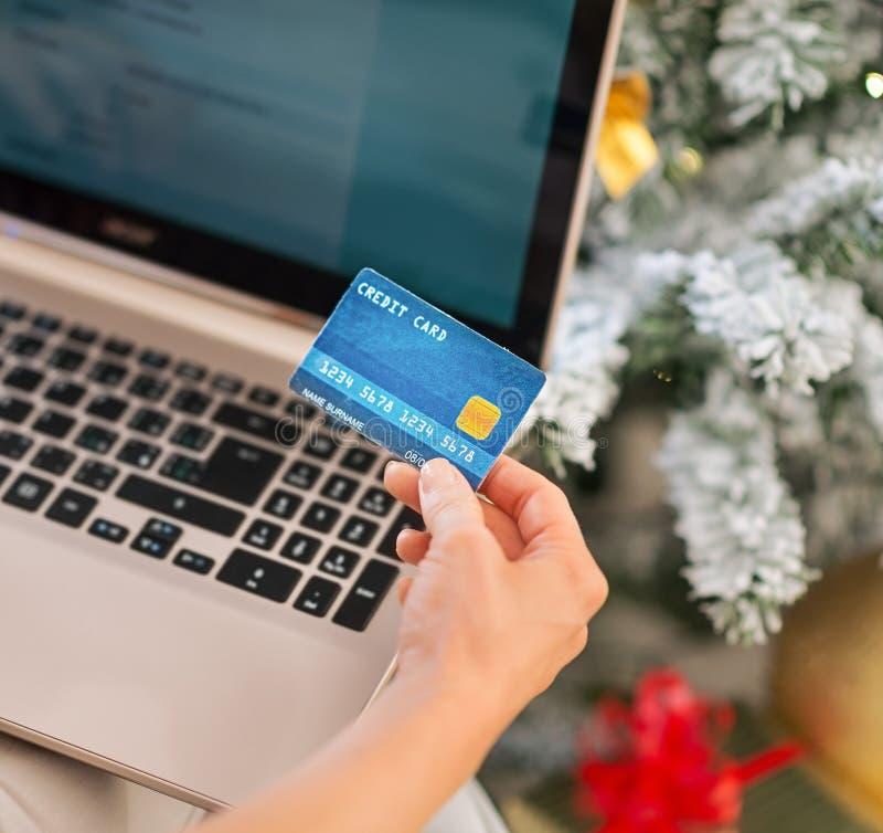 Plan rapproché sur la femme faisant des achats en ligne près de l'arbre de Noël photographie stock libre de droits