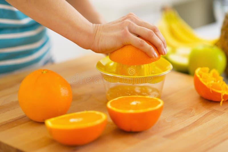 Plan rapproché sur la femme faisant le jus d'orange photo stock