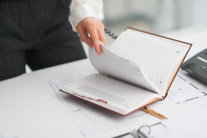 Plan rapproché sur la femme moderne d'affaires vérifiant le bloc-notes images stock