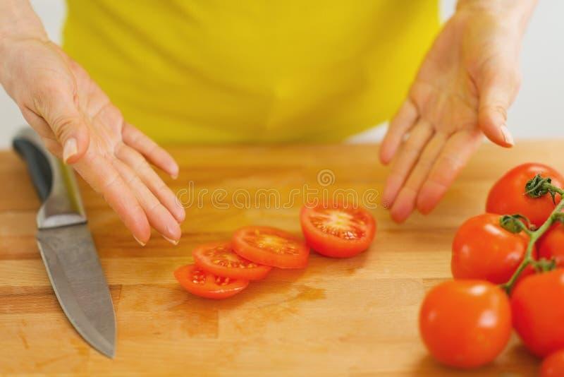 Plan rapproché sur la femme montrant des tranches de tomate sur la planche à découper image stock