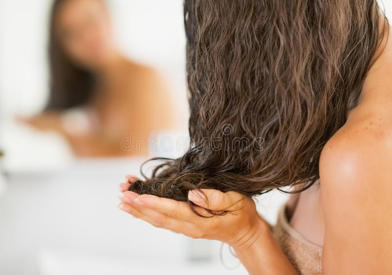 Plan rapproché sur la jeune femme appliquant le masque de cheveux photos stock