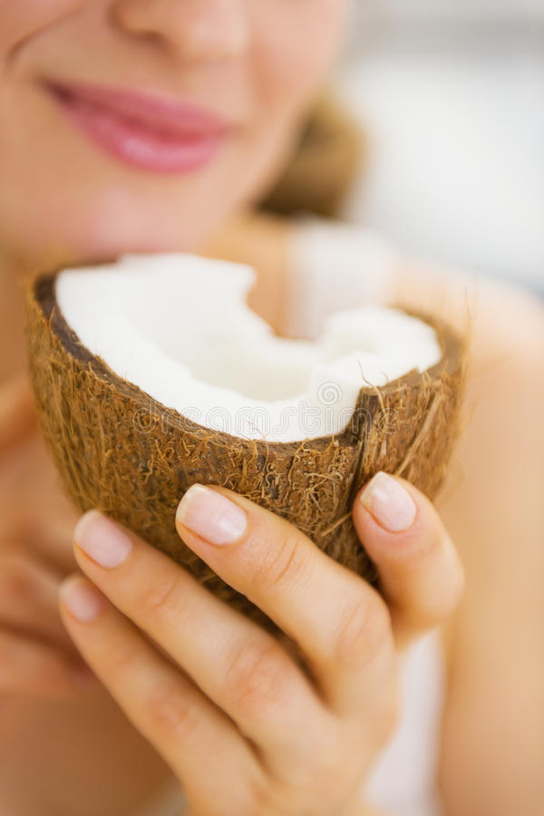 Plan rapproché sur la jeune femme appréciant la noix de coco image stock