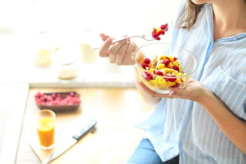Plan rapproché sur la jeune femme au foyer mangeant de la salade de fruit frais images stock