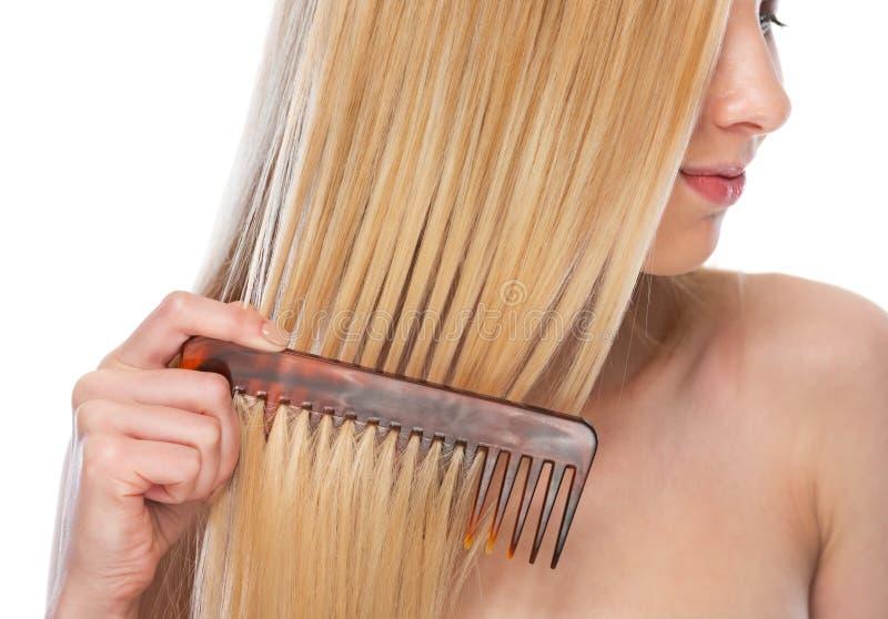 Plan rapproché sur la jeune femme peignant des cheveux photos stock