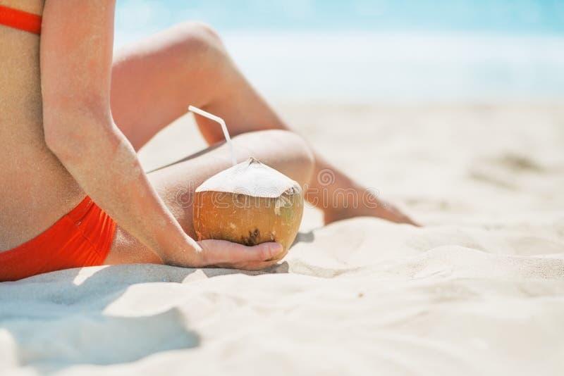 Plan rapproché sur la jeune femme s'asseyant avec la noix de coco photo libre de droits