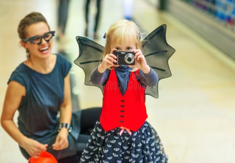 Plan rapproché sur la mère et l'enfant prenant la photo avec l'appareil photo numérique images stock