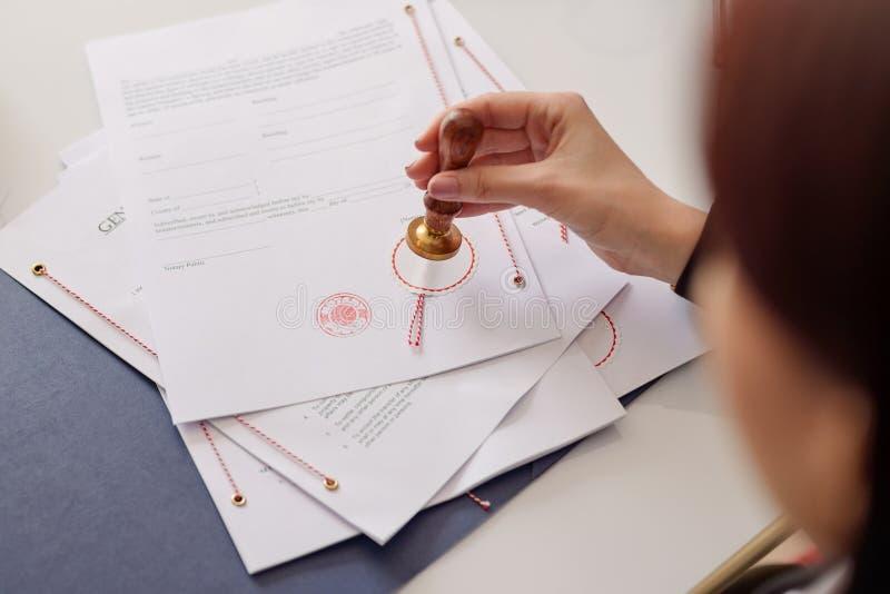 Plan rapproché sur la main de notaire emboutissant le document photo libre de droits