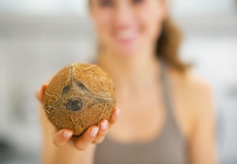 Plan rapproché sur la noix de coco à disposition de la jeune femme photos stock
