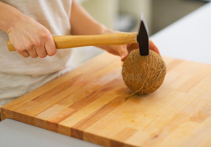Plan rapproché sur la noix de coco d'ouverture de femme utilisant le marteau photo libre de droits