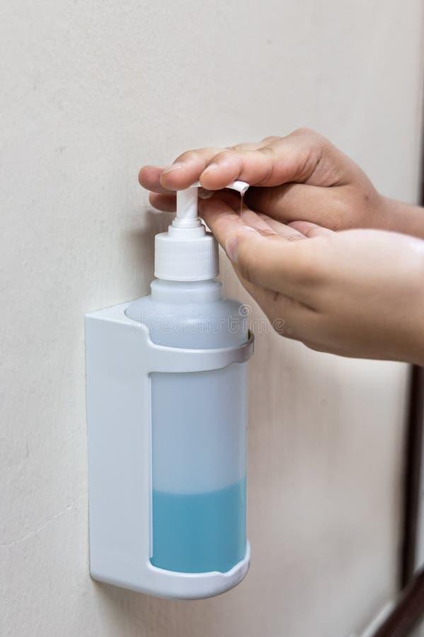 Plan rapproché sur la personne distribuant le liquide désinfectant d'aseptisant sur image libre de droits