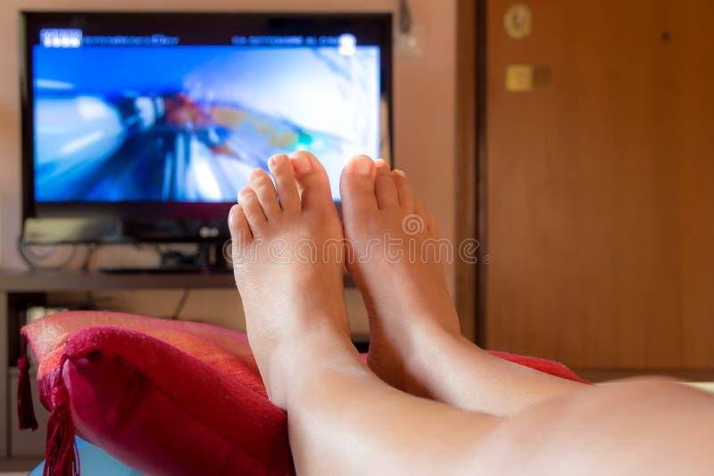 Plan rapproché sur les pieds d'une fille regardant la TV photographie stock