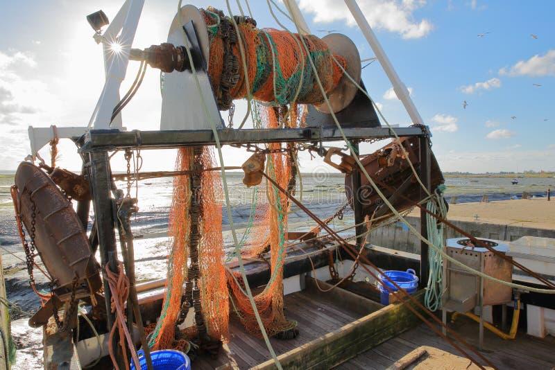 Plan rapproché sur un chalutier de pêche coloré amarré au quai avec la plage boueuse à marée basse à l'arrière-plan, Leigh sur la image stock