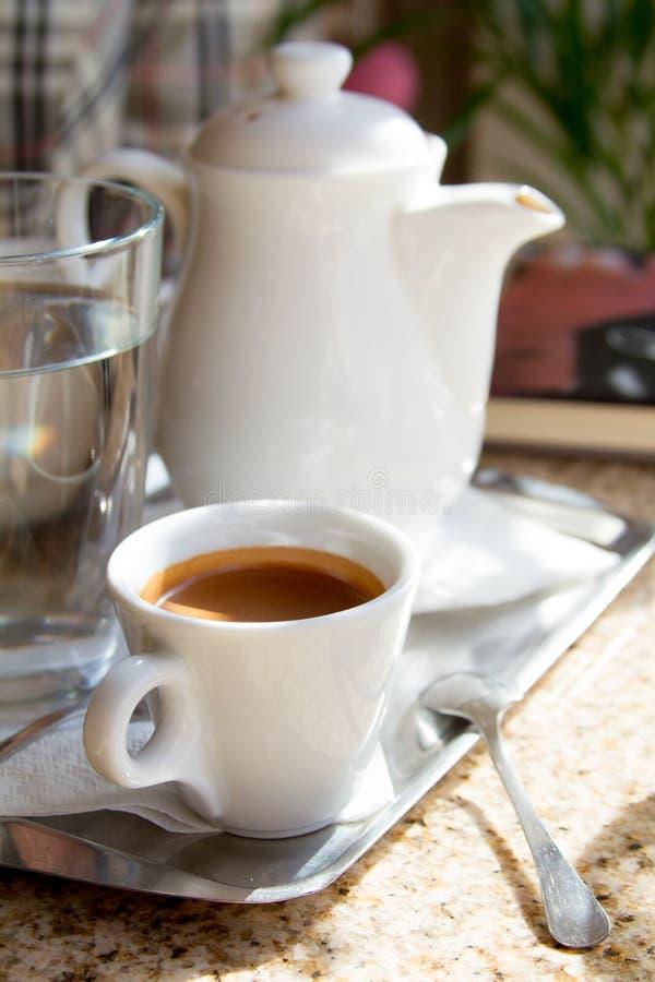 Plan rapproché sur un pot blanc de café de porcelaine de plateau et une tasse avec l'expresso fraîchement brassé sur la terrasse, image stock