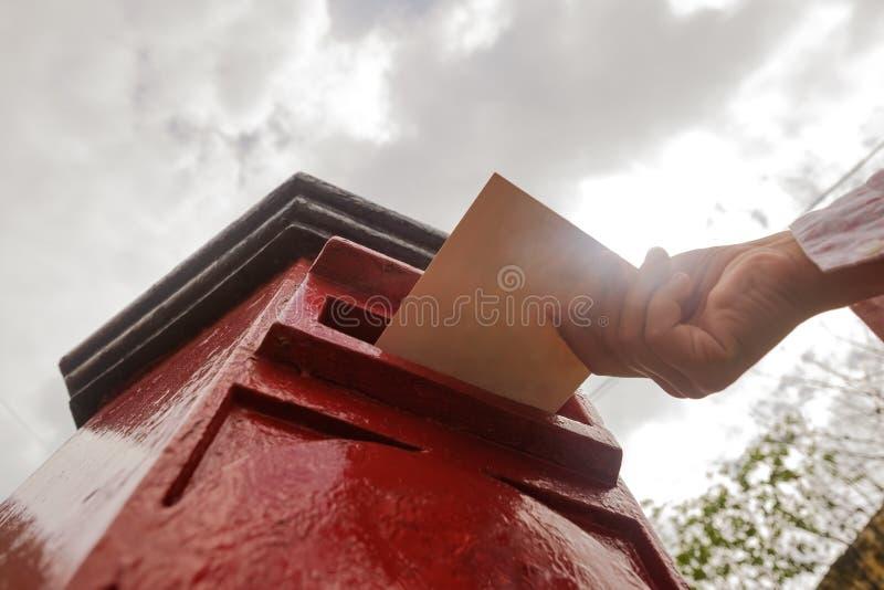 Plan rapproché sur une main masculine mettant une lettre dans une boîte à marquer d'une pierre blanche Concept de type de vintage photo libre de droits