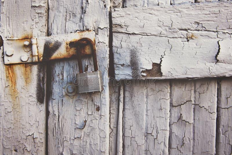 Plan rapproché tiré d'un vieux cadenas rouillé sur une porte blanche superficielle par les agents en bois images stock