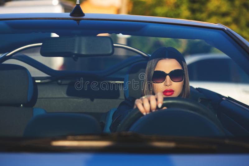 Plan rapproché tiré de la fille élégante de brune avec les lèvres rouges utilisant des lunettes de soleil conduisant un cabriolet photographie stock libre de droits