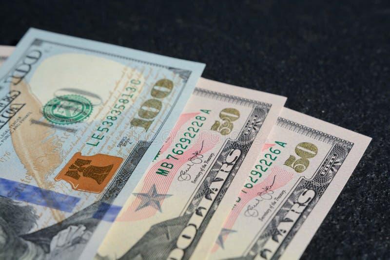 Plan rapproché tiré des cent deux quinze dollars d'Etats-Unis sur un fond gris-foncé photo libre de droits