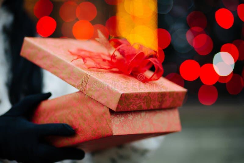 Plan rapproché tiré des mains femelles dans les gants tenant le boîte-cadeau au b photos libres de droits