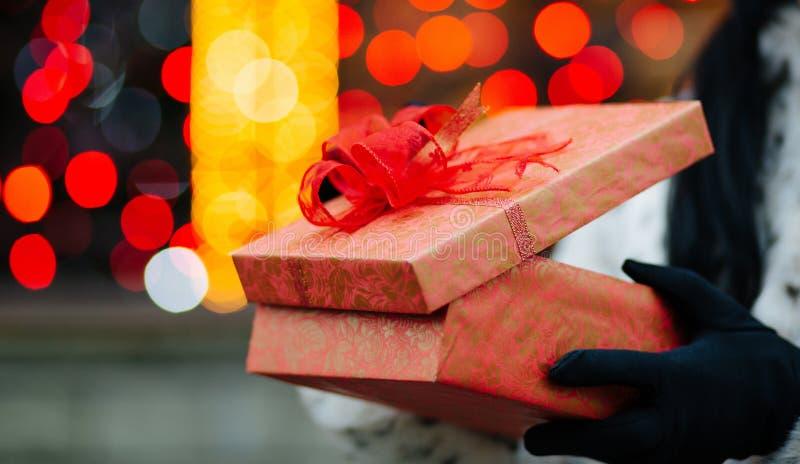 Plan rapproché tiré des mains femelles dans les gants tenant le boîte-cadeau au b image libre de droits