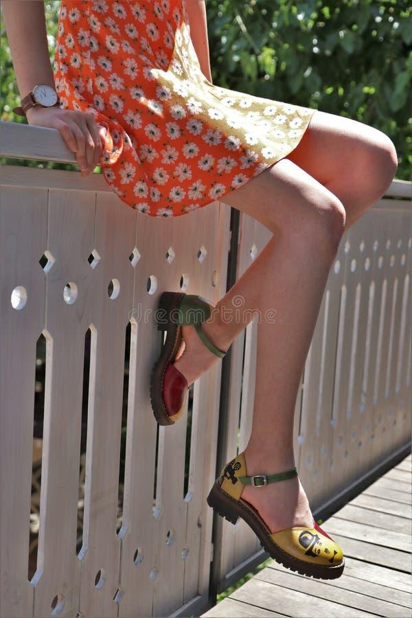 Plan rapproché tiré des pieds élégants d'une femelle portant une robe à l'été photographie stock libre de droits