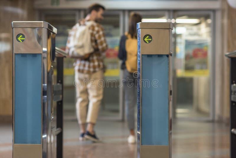 plan rapproché tiré des tourniquets et des couples des voyageurs avec des sacs à dos images libres de droits