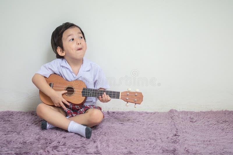 Plan rapproché un petit enfant dans l'ukulélé uniforme de jeu d'étudiant sur le tapis avec l'espace de copie photo stock
