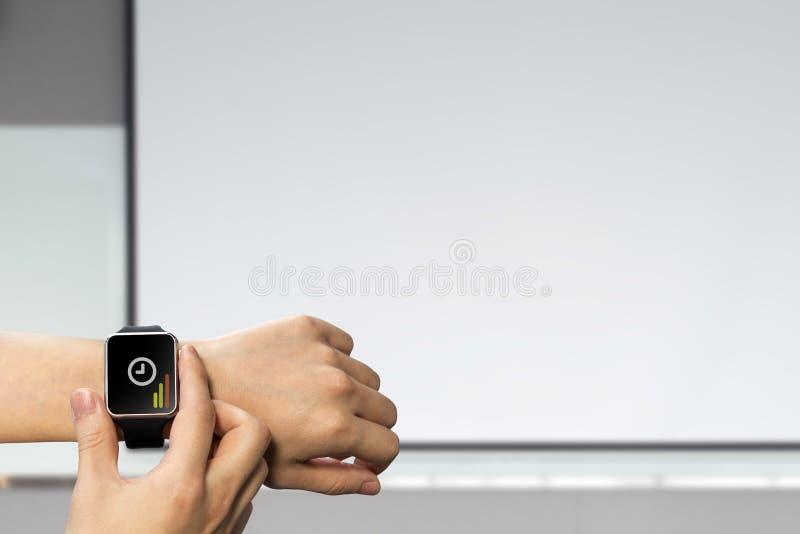 Plan rapproché vérifiant la montre intelligente et l'APP image stock